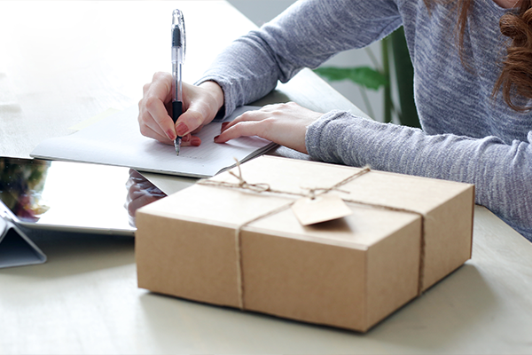 Woman writing a note to go with a package